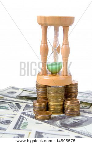 Hourglass On  A Pile Of Coins On White Background