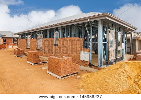 Construction site with homes from brick with metal framing against a blue sky.House construction site