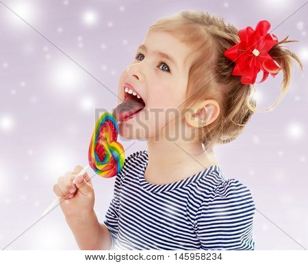 Cute little blonde girl with a red bow on her head, with pleasure licking colorful candy on a stick. Visible language which was painted in a candy color. Close-up.On new year purple background with white snowflakes.