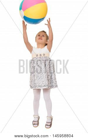 Cheerful Caucasian little girl in grey short dress jumping . The girl photographed at the time of the jump. Girl catches the ball in flight - Isolated on white background