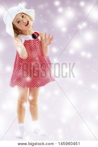 Joyful little girl in a very short polka dot dress and white Panama city beach , claps.Full growth.On new year purple background with white snowflakes.