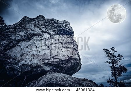 Boulders against sky with cloudy and beautiful full moon over tranquil nature outdoor at the nighttime. Beauty landscape from national park. The moon were NOT furnished by NASA.