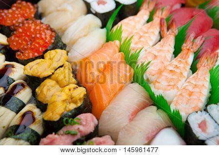 Japanese Sushi arranged on a traditional sushi tray.