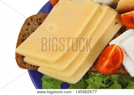 set of gourment cheese slice and chunk ( bar)  white goat greek yellow french aged on half of rye bread on green lettuce salad with tomatoes on blue plate isolated over white background