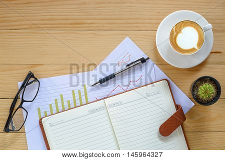 Office desk table with eyeglass leather notebookpenanalysis chart and cup of coffee .Top view with copy space.Office desk table concept.Office supplies and gadgets on desk table.