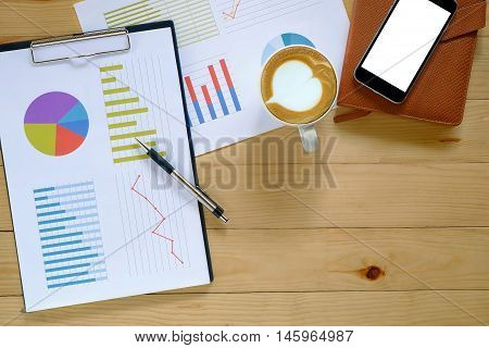 Office desk table with blank screen smartphone leather notebookpenanalysis chart and cup of coffee .Top view with copy space.Office desk table concept.Office supplies and gadgets on desk table.