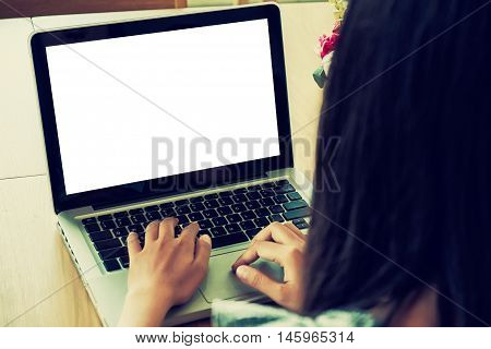 Close up of young woman using laptop computer on wooden table with blank screen laptop computer.Business concept.Young woman hands holding keyboard.Vintage tone