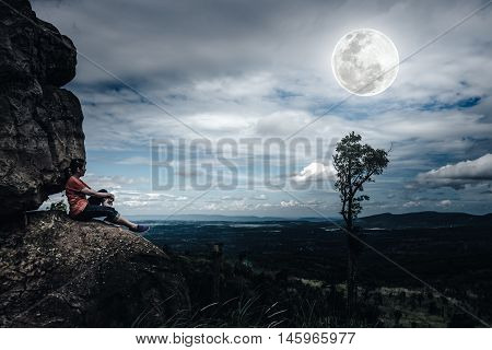Woman sitting on boulders and looking at sky with cloudy and beautiful full moon over tranquil nature nighttime. Beauty landscape from national park. The moon were NOT furnished by NASA.