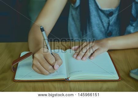 Girl hands with pen writing on leather notebook.Beautiful hand holding pen for writing.Vintage tone