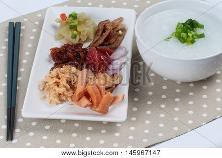 Rice gruel and  side dish  on brown napery. (Dried shredded pork,Chinese sausage,crispy fish,sausage, fried baby clams,sliced red onion,pickle Chinese cabbage ,Spicy sardine salad and shallots )