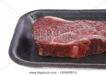 fresh raw marble beef meat steak on black plastic market tray isolated on white background
