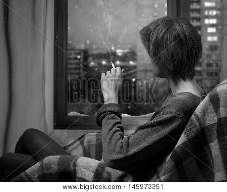 A woman smokes a cigarette while sitting in a chair. Outside the window the snow falls. Evening city block the windows of houses. A woman looks out the window. A warm blanket. Black and white