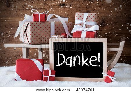 Chalkboard With German Text Danke Means Thank You. Sled With Christmas And Winter Decoration And Snowflakes. Gifts And Presents On Snow With Wooden Background.