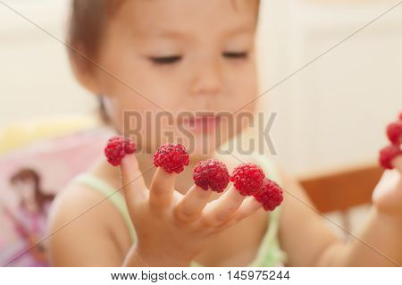 Little Girl With Raspberry On Fingers