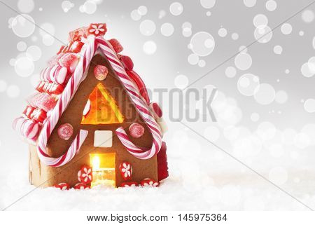 Gingerbread House In Snow As Christmas Decoration. Candlelight For Romantic Atmosphere. Silver Background With Bokeh Effect. Copy Space For Advertisement