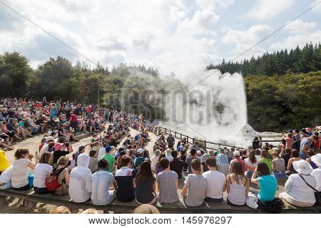 Rotorua, New Zealand - February 25, 2015: Tourists watching the eruption of Lady Knox geyser in Wai-o-Tapu National Park