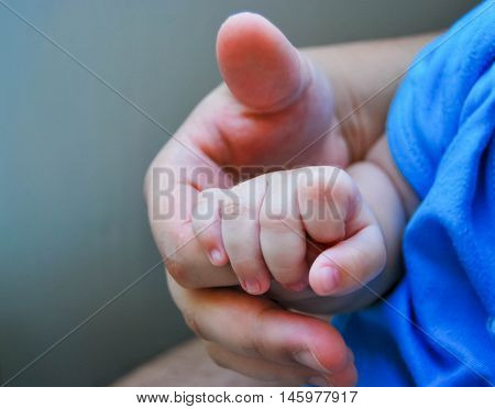 Baby hand in father's hand. childhood. family