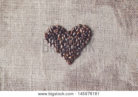 Burlap texture with coffee beans heart shape background, love symbol. Sack cloth canvas with copy space. Seeds at hessian textile, soft color toning