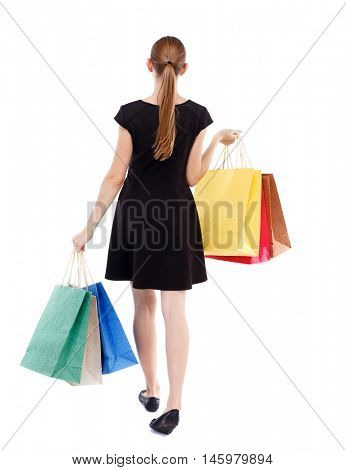 back view of going woman with shopping bags . Rear view people collection. Isolated over white background. Blonde in a short black dress shopping.