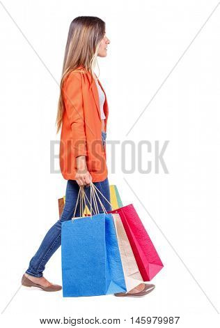 side view of going woman with shopping bags .girl in a red jacket carries shopping bags in the side.