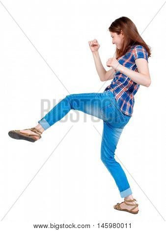 back view of woman funny fights waving his arms and legs. Girl in plaid shirt has a foot.