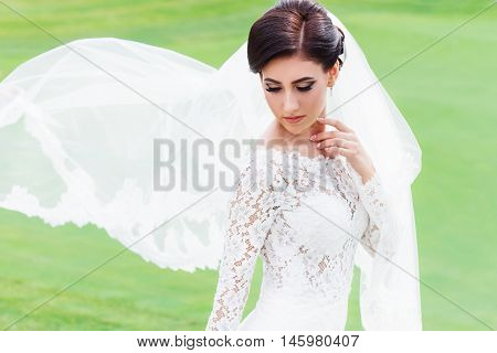 portrait of beautiful bride in wedding dress with fluttering veil on the green field of the golf club. Bride with long veil fluttering in the wind. Wedding magazine advertising model banner poster dress bride