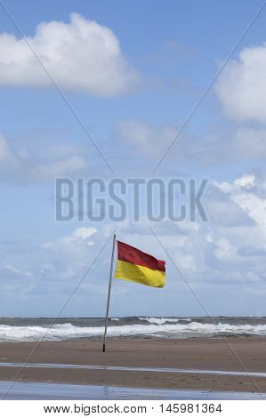 red and yellow flag on dutch beach of the island vlieland as warning sign for storm