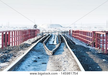 Railway bridge and deformation of the railway track, built on permafrost. Polar tundra, Russia.