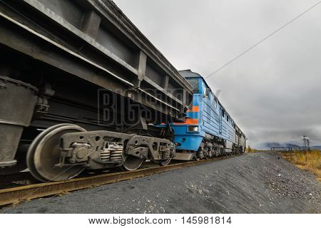 The diesel locomotive is a freight train. Polar tundra, late autumn, cloudy day.