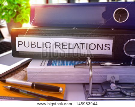 Black Ring Binder with Inscription Public Relations on Background of Working Table with Office Supplies and Laptop. Public Relations Business Concept on Blurred Background. 3D Render.