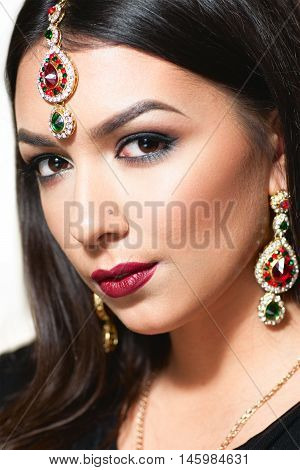 Beautiful Indian woman portrait with golden jewelry. Gorgeous arabic girl eyes. Beautiful Hindustani princess