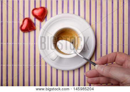 female hand with a teaspoon of sugar to sweeten a cup of coffee and two chocolate heart