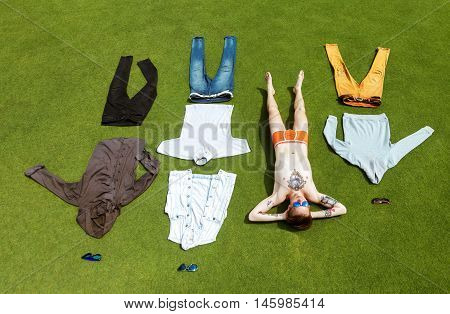 Fashion man lies undressed on greed grass background with his clothes allocated like in wardrobe