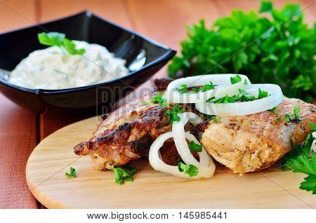 Skewers with onions and parsley on a wooden table. White sauce and a bunch of parsley in the background