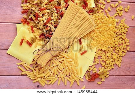 Colored macaroni, spaghetti and lasagna on a wooden background