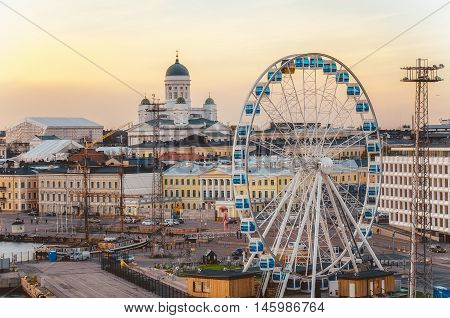 Helsinki Finland - March 17 2015: View of the Ferris wheel and Cathedral St Nicholas Church at sunset in Helsinki Finland.