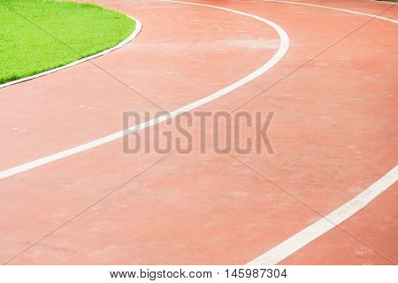 Running track and green field in sport park in evening time