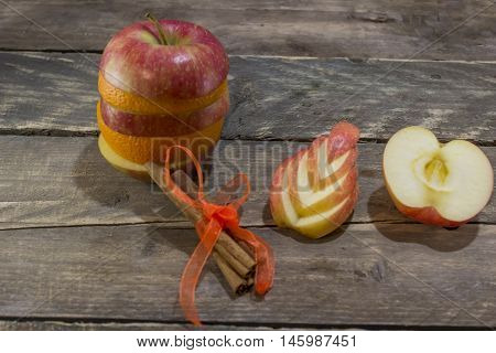 Mix of ripe apple and orange with sticks of cinnamon on a wooden desk .