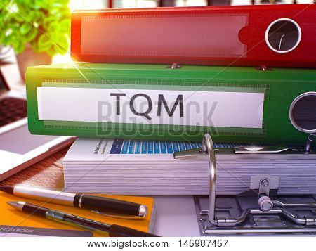 Green Office Folder with Inscription TQM - Total Quality Management - on Office Desktop with Office Supplies and Modern Laptop. TQM Business Concept on Blurred Background. TQM - Toned Image. 3D.