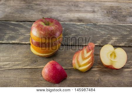 Mix of ripe apple and orange on a wooden desk