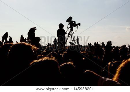 silhouette of cameraman operator shooting a live rock concert, fans around raised hands