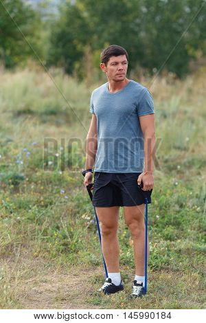 Handsome young muscular sports man exercising outside outdoor with rubber band. Fit fitness exercise workout and healthy lifestyle concept.