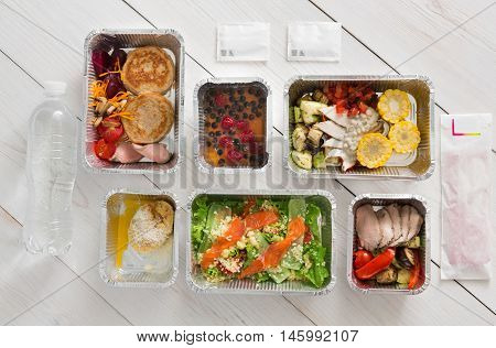 Healthy food delivery, daily ration. Take away of natural organic low carb diet. Fitness nutrition with water bottle in foil boxes. Top view, flat lay at white wood
