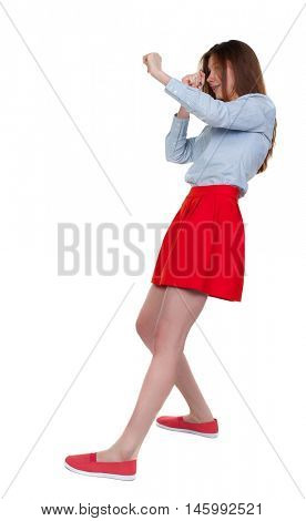 skinny woman funny fights waving his arms and legs. Long-haired brunette in red skirt leaned protected from impact.