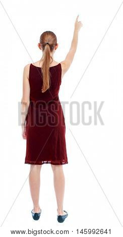 Back view of pointing woman. beautiful girl. Isolated over white background. A girl in a burgundy dress sleeveless see what interesting things in the sky.