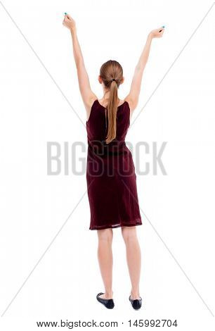 Back view of woman. Raised his fist up in victory sign. backside view of person. Isolated over white background. A girl in a burgundy dress sleeveless happily raised his hands up.