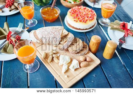 Rough wooden dinner table filled with simple but exquisitely decorated dishes, cake with red berries, silverware and napkins with ribbon bows, focus on sliced bread, walnuts and cheese chunks