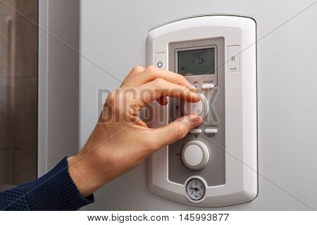 Men hand regulate high temperature on 75 degree in control panel of central heating.