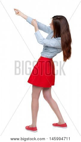 back view of standing girl pulling a rope from the top or cling to something. Long-haired brunette in red skirt pulling a rope from the top side