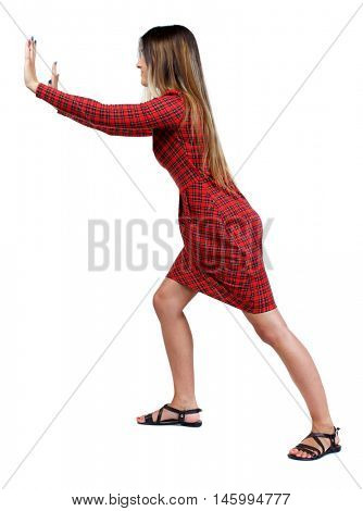 back view of woman pushes wall. Isolated over white background. girl in red plaid dress stands sideways and pushing his hands something to the side.